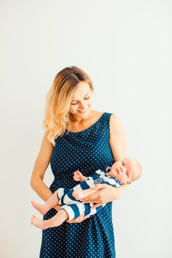 Молодая привлекательная мать с newborn младенцем в ее оружиях стоковая фотография