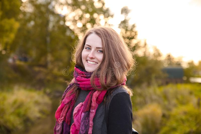Молодая привлекательная рыжеволосая девушка представляя для портрета на ба стоковые фото