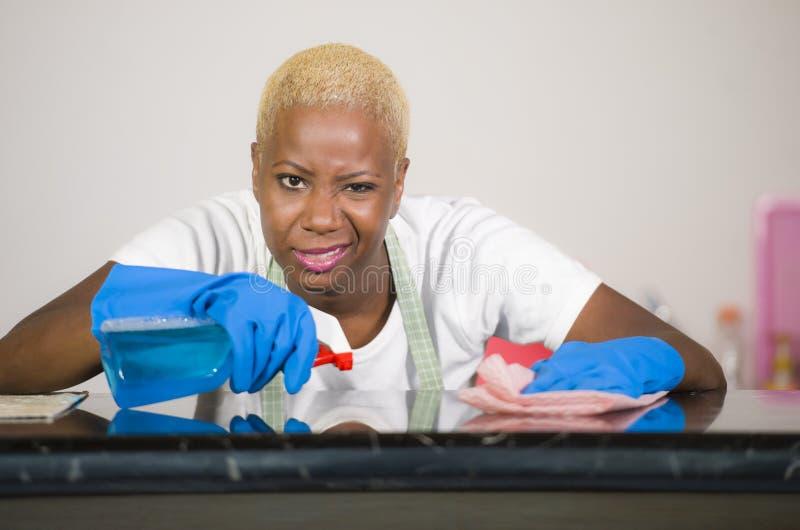 Молодая привлекательная усиленная и расстроенная назад афро американская женщина в моя резиновых перчатках очищая домашнюю кухню  стоковое изображение rf