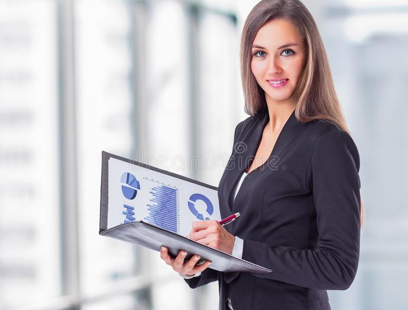 Молодая, привлекательная, успешная бизнес-леди, изучает диаграммы стоковое фото rf