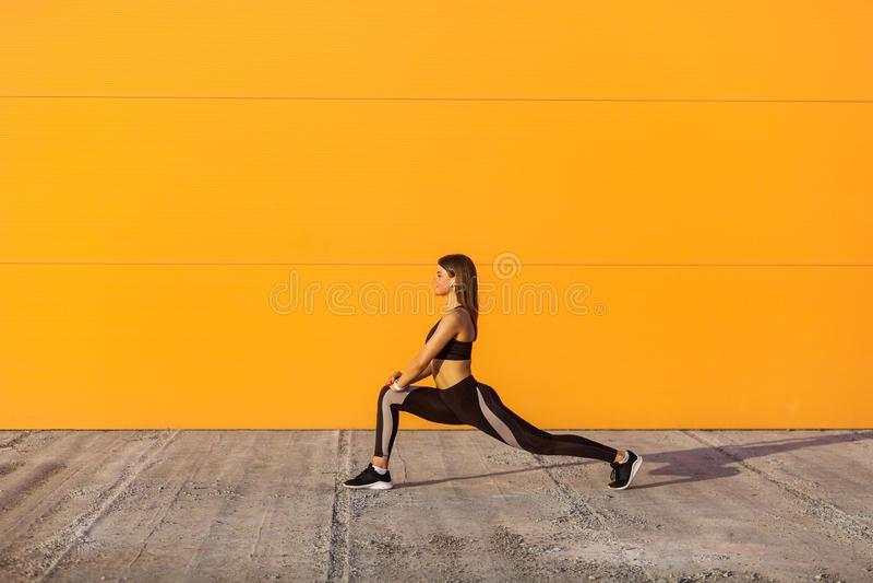 Молодая привлекательная sporty женщина нося тренировки спорта черного sporwear практикуя в утре на улице, протягивающ ноги и стоя стоковые фотографии rf