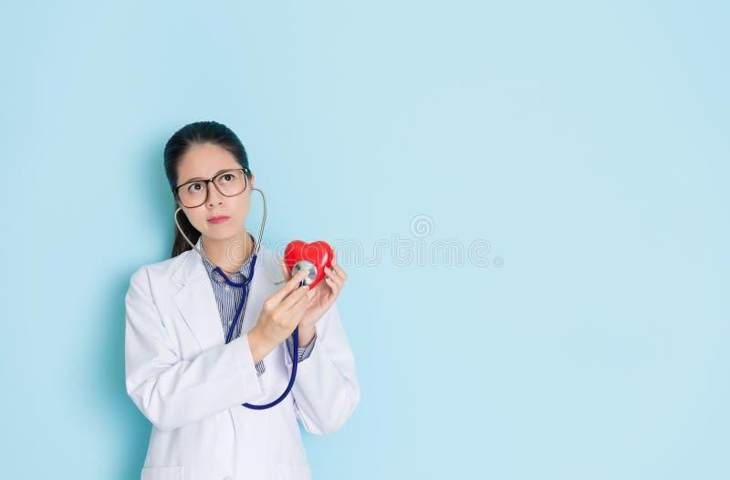 Молодая профессиональная женщина доктора держа сердце стоковое изображение rf