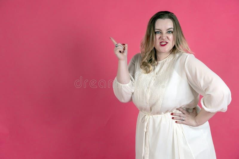 Молодая пухлая женщина в белом платье с голубыми глазами показывает ее палец на космосе экземпляра стоковые изображения rf