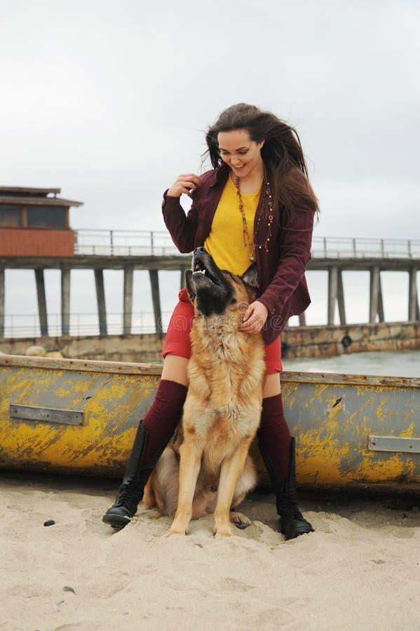 Молодая радостная девушка играя с ее собакой немецкой овчарки стоковое изображение rf