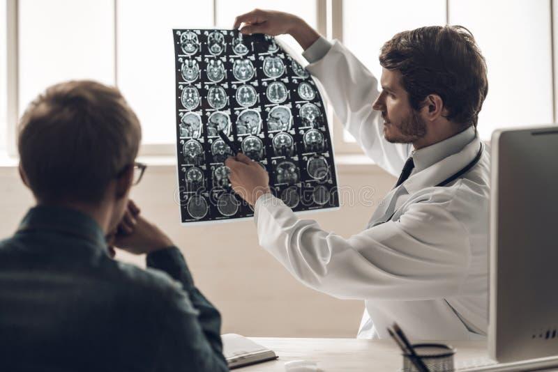 Молодая развертка доктора Showing MRI мозга к пациенту стоковое фото rf