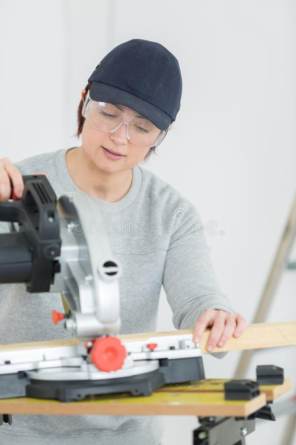Молодая разделочная доска woodworker взрослой женщины в мастерской стоковое изображение
