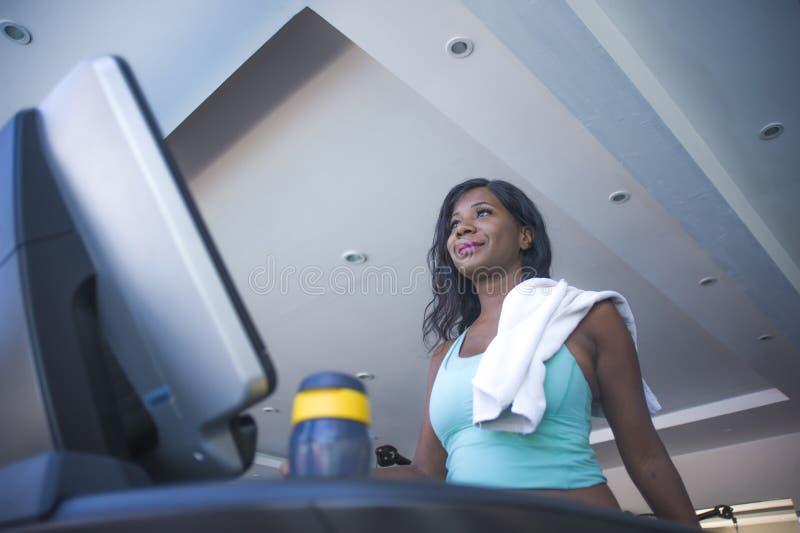 Молодая разминка привлекательного и потного черного афро американского третбана тренировки женщины бежать и идя на усмехаться фит стоковое изображение rf