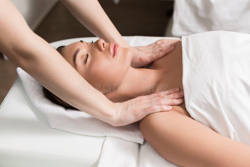 молодая расслабленная женщина при закрытые глаза имея массаж тела в салоне курорта стоковое фото rf