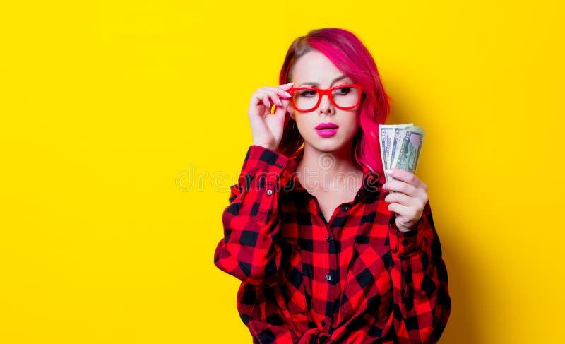 Молодая розовая девушка волос в красной рубашке тартана с деньгами стоковая фотография rf