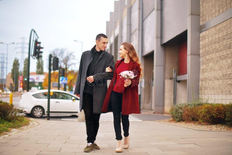 Молодая романтичная пара, красивая девушка с цветками имеет датировка в городе Человек в серой шинели и модель в красном пальто стоковые фотографии rf