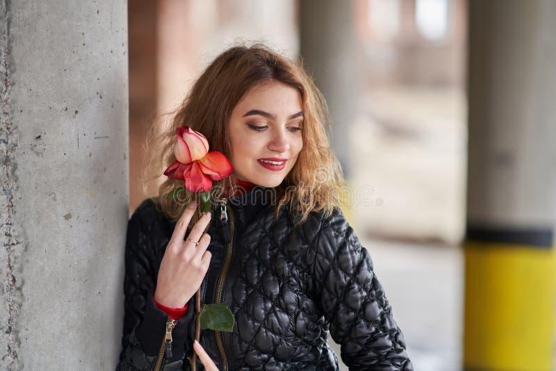 Молодая рыжеволосая девушка в черной куртке представляя с красной розой в ее руке стоковое фото rf