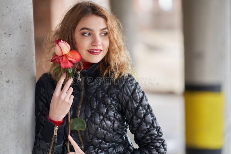 Молодая рыжеволосая девушка в черной куртке представляя с красной розой в ее руке стоковое изображение rf
