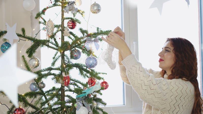 Молодая рыжеволосая женщина украшая рождественскую елку с игрушками окном стоковое фото rf