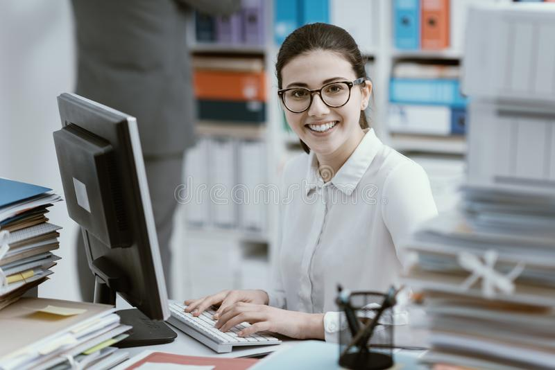 Молодая секретарша работая и усмехаясь стоковая фотография