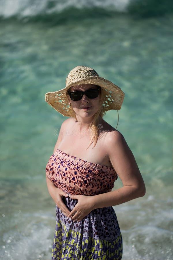 Молодая сексуальная белокурая женщина в платье пляжа около моря стоковое фото