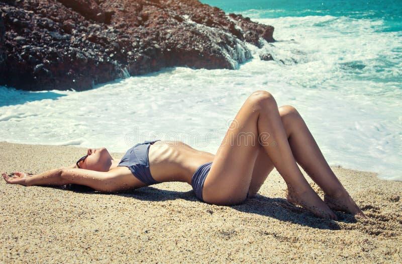 Молодая сексуальная женщина в бикини ослабляя на тропическом пляже Принципиальная схема каникулы лета стоковая фотография rf