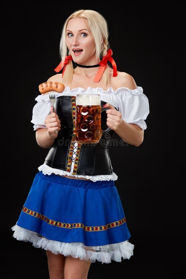 Молодая сексуальная женщина нося dirndl с кружкой пива на черной предпосылке стоковые изображения