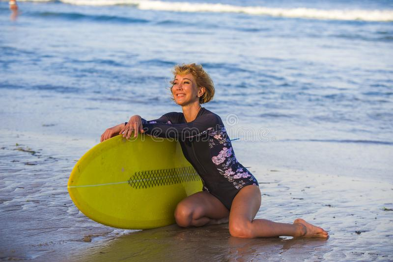 Молодая сексуальная красивая и счастливая женщина серфера сидя на песке пляжа держа желтое holid лета доски прибоя усмехаясь жизн стоковые фотографии rf