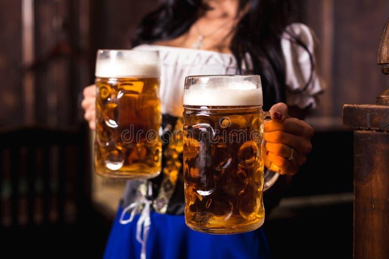 Молодая сексуальная официантка Oktoberfest, носящ традиционное баварское платье, служа большие кружки пива на баре стоковые изображения