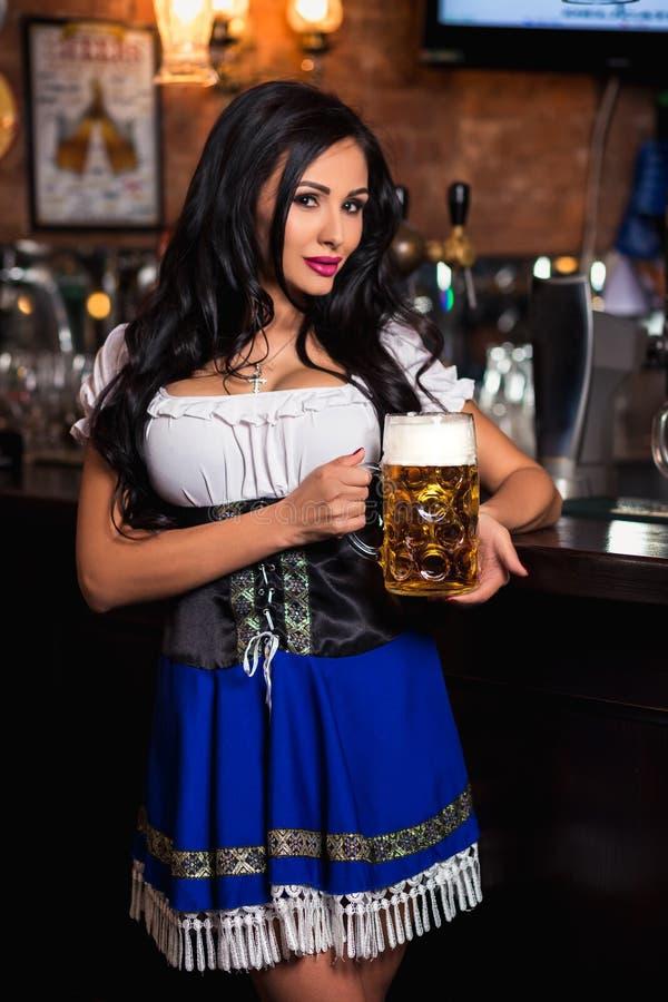 Молодая сексуальная официантка Oktoberfest, носящ традиционное баварское платье, служа большая кружка пива стоковое изображение