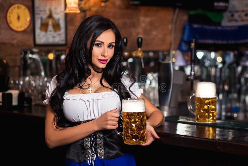 Молодая сексуальная официантка Oktoberfest, носящ традиционное баварское платье, служа большая кружка пива стоковое фото