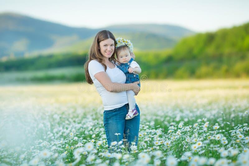 Молодая семья в поле жизни спа стоцвета помостов цветков anjoy счастливой вместе с милыми сторонами в движении деревни деревенско стоковые изображения rf