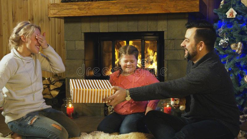 Молодая семья давая подарки рождества одина другого стоковая фотография rf