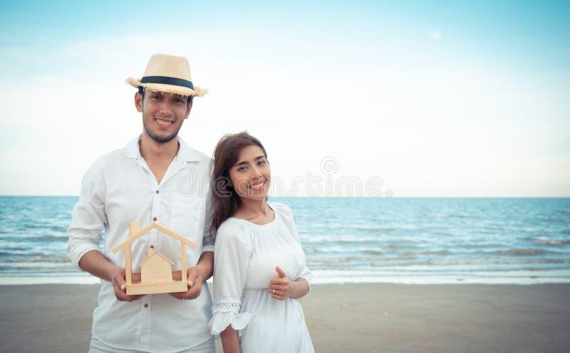 Молодая семья держа деревянный дом на пляже стоковое изображение rf