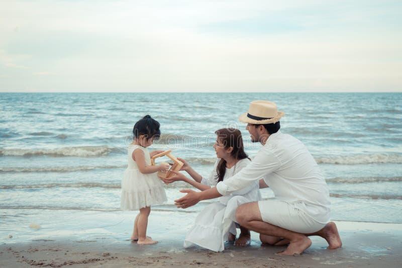 Молодая семья держа деревянный дом на пляже стоковая фотография rf