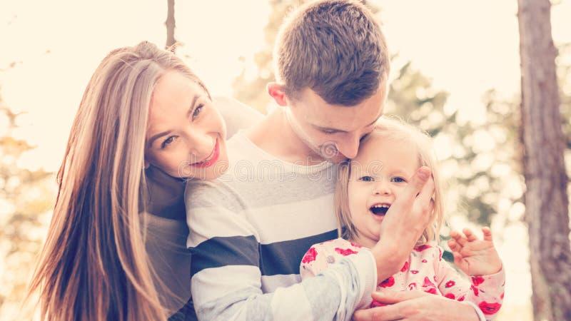 Молодая семья из трех человек имея потеху в парке наслаждаясь их временем совместно Реальные люди, концепция подлинности стоковое фото rf