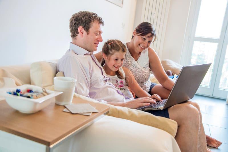 Молодая семья используя ноутбук сидя на софе дома Усмехаясь родители с их дочерью имея видео потехи наблюдая стоковое изображение