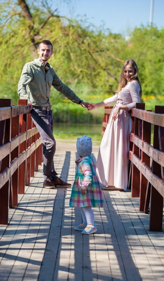 Молодая семья, мать, отец, дочь, прогулка в парке города стоковые фото