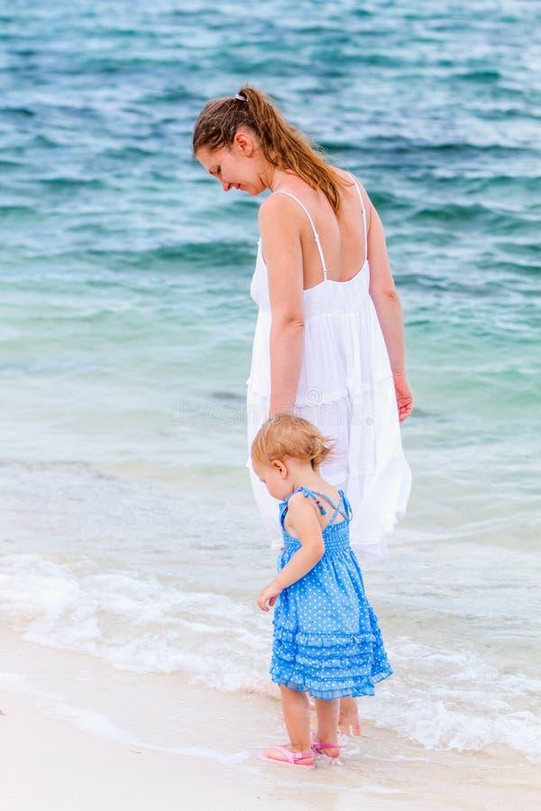 Молодая семья на пляже стоковое фото