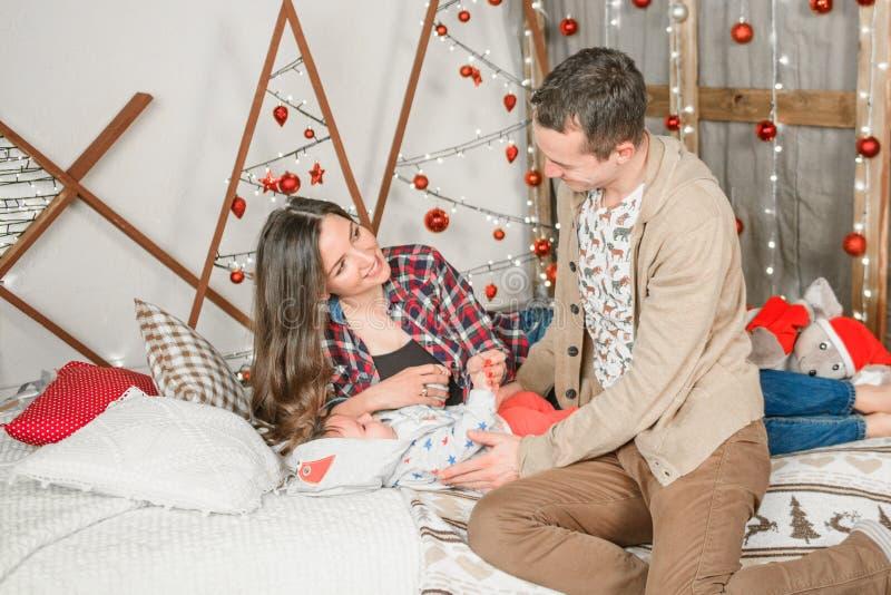 Молодая семья на Рождество отпразднуйте новый год вместе со своими близкими счастливая семья отец и ребенок с магическим подарком стоковые изображения