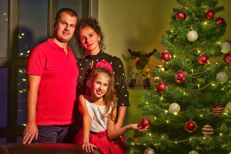 Молодая семья празднует Рождество дома Счастливой молодой семье стоковые фотографии rf