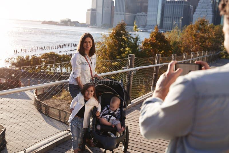 Молодая семья при 2 дочери принимая фото на footbridge стоковые фотографии rf