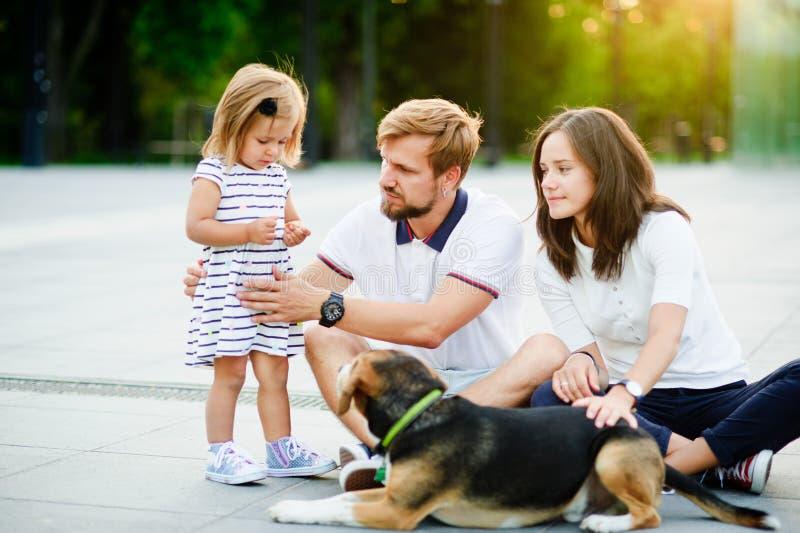 Молодая семья проводя выходной день в парке города стоковое изображение rf
