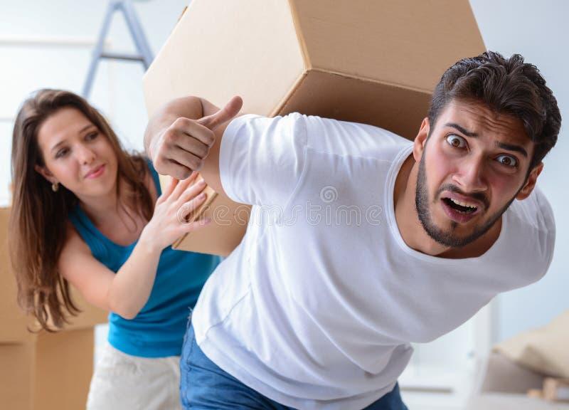 Молодая семья распаковывая на новом доме с коробками стоковое изображение