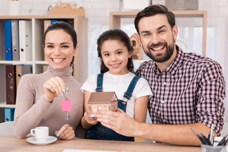 Молодая семья счастлива купить новый дом, держащ ключи от дома и миниатюрного дома стоковые фотографии rf
