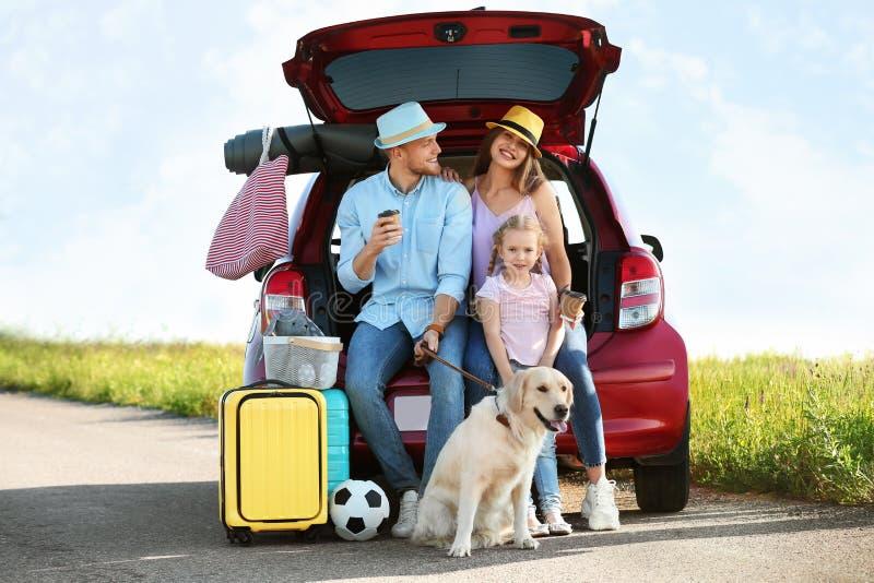 Молодая семья с багажом и собакой около багажника автомобиля стоковые изображения