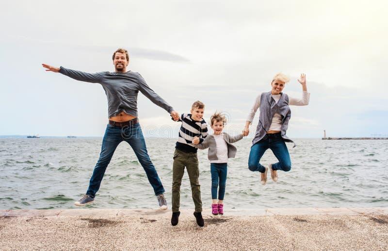 Молодая семья с 2 небольшими детьми скача outdoors на пляж, держа руки стоковое изображение rf