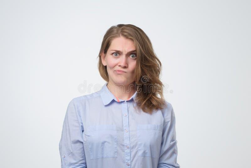 Молодая серьезная сердитая женщина с длинными волосами выглядя подозрительный стоковые фотографии rf