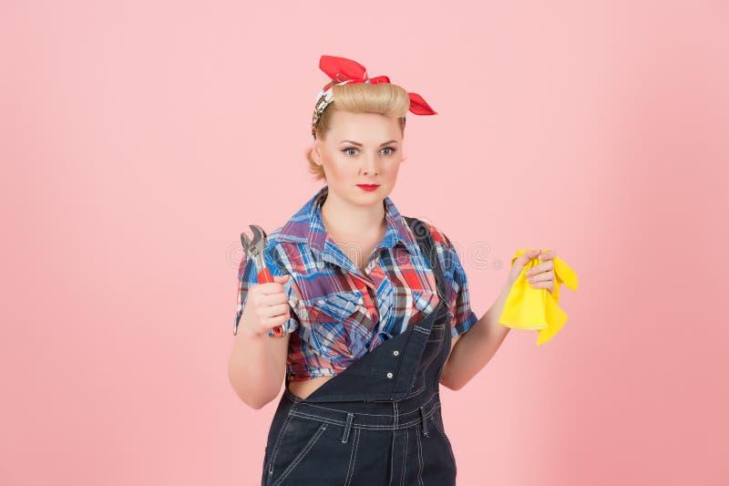 Молодая сильная женщина в неудовлетворенном стиле штыря-вверх держащ желтые перчатки и ключ латекса изолированными на пастельн-ро стоковые фотографии rf