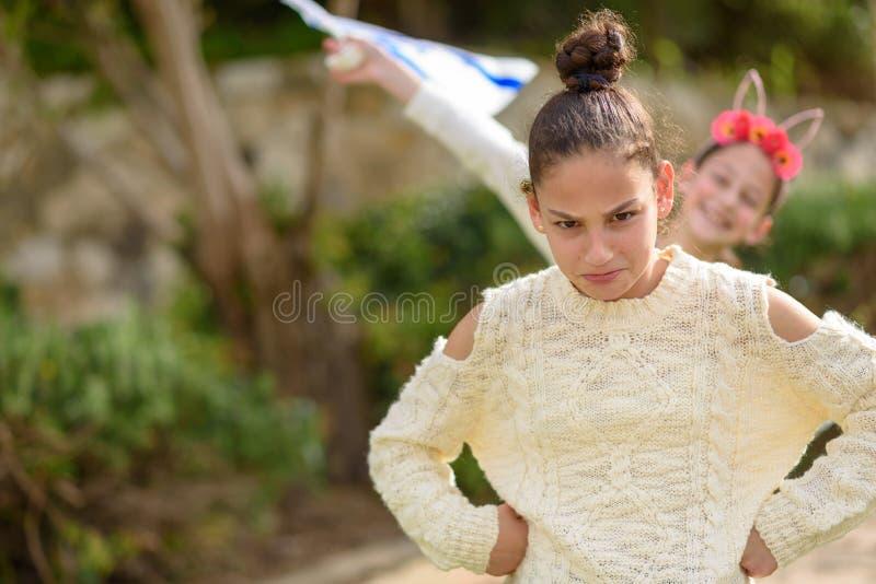 Молодая смешная девушка подростка стоя на открытом воздухе с оружиями подбоченясь стоковое изображение rf