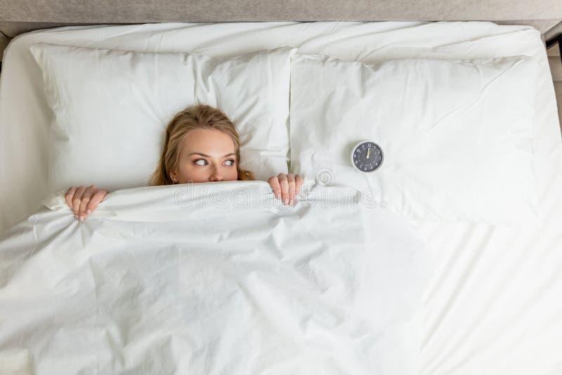 Молодая смешная красивая женщина смотря будильник пока лежащ на кровати стоковые фотографии rf