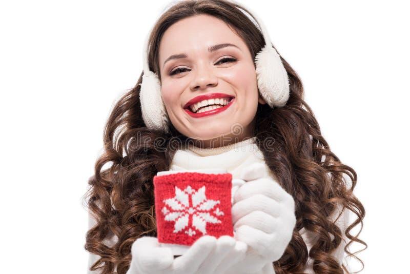 молодая смеясь над женщина в шарфе, перчатках и earmuffs держа кофейную чашку в свитере кружки, стоковое изображение