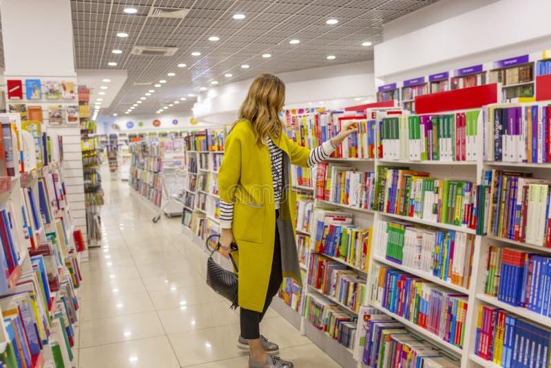 Молодая современная женщина в большом bookstore стоковое изображение rf