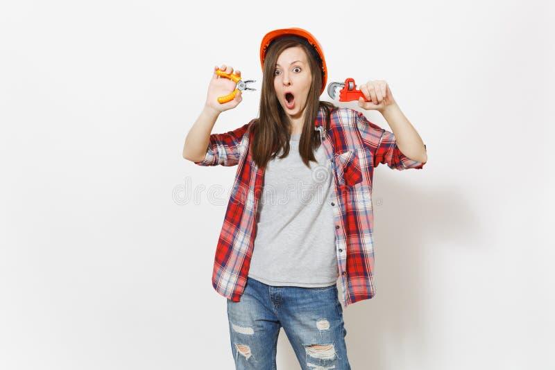 Молодая сотрясенная женщина в случайных одеждах, шлем защитной конструкции оранжевый держа инструменты здания игрушки изолированн стоковое фото rf