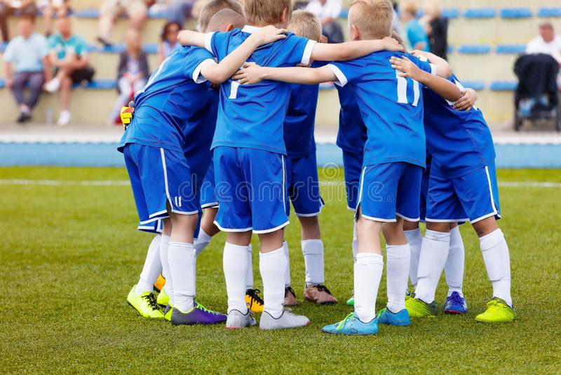 Молодая спортивная команда мальчиков на стадионе Футболисты в sportswear мотируя перед спичкой стоковые изображения rf