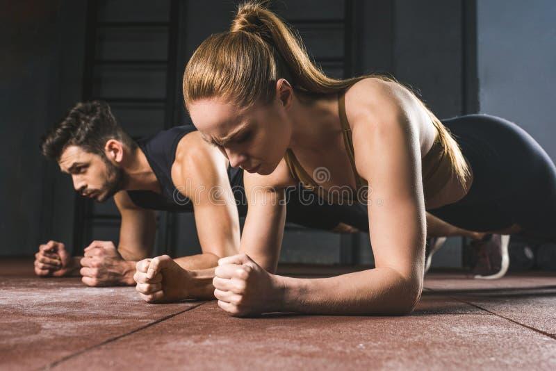 Молодая спортсменка и спортсмен делая планку стоковое изображение rf